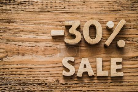 - 30 percent discount icon symbol on a wooden background. Minus thirty