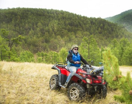 Motorsport With the ATV. Excited young man on quad bike. Happy young man driving all terrain vehicle in nature.