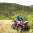 Постер, плакат: Motorsport With the ATV Excited young man on quad bike Happy young man driving all terrain vehicle in nature