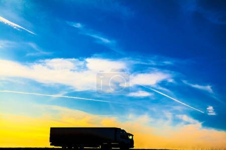 Silhouette of a moving truck at sunset. Truck on asphalt highway in a rural landscape at sunset.