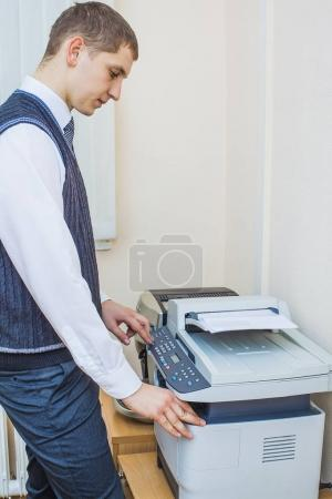 man pressing the start button on a multi function printer