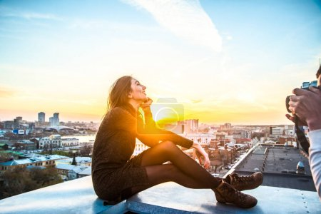 young woman sitting  on house roof against blue sunset sky and big city