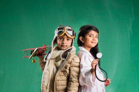 Photo pour Enfants et concept éducatif - Petit garçon et fille indien posant devant le panneau de craie verte en robe fantaisie pilote et costume de médecin avec stéthoscope, vous voulez pilote ou médecin - image libre de droit