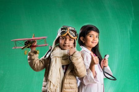 Photo pour Enfants et l'éducation concept - petit garçon indien et fille posant devant jury de craie verte en costume de médecin et de déguisements pilote avec stéthoscope, envie de pilote ou un médecin - image libre de droit