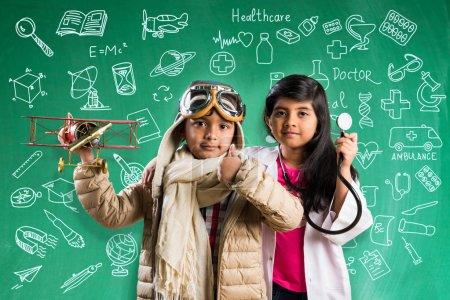 Photo pour Enfants et l'éducation concept - petit garçon indien et fille posant devant le tableau de craie verte avec griffonnages en pilote de déguisements et costume de médecin avec stéthoscope, veulent être pilote ou votre médecin - image libre de droit