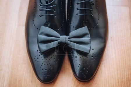 Close-up, top view of modern accessories for men. Black bow tie, leather shoes on a wooden background.