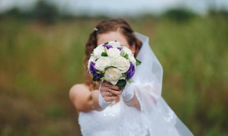 bride covers her face with a wedding bouquet of white roses on a background of nature.