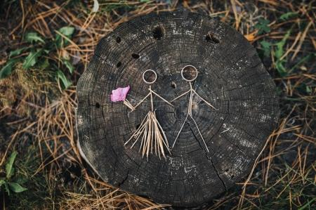 Wedding rings instead of the heads of the bride and groom. Crafts from Christmas-tree needles in the form of a bride and groom. The bride and groom happily hold hands.