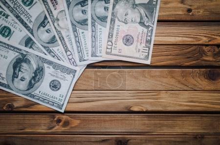 Dollars on a wooden table. Banknotes of denomination 100, 50, 10. Top view. Copy space.