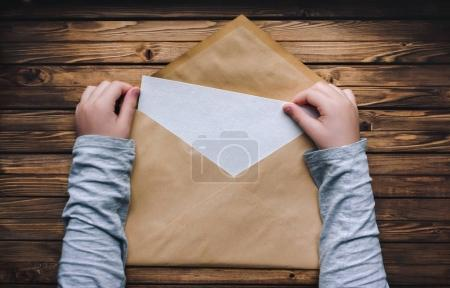 large brown envelope holds the child's hands. Open envelope on a wooden background. A blank sheet of paper in an envelope.