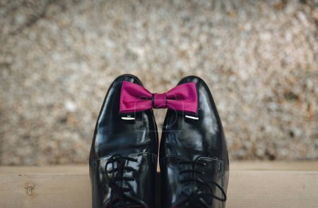 Groom's accessories. Leather shoes on a stone background with a bow tie and cufflinks on shoes of patent leather. Top view , bokeh