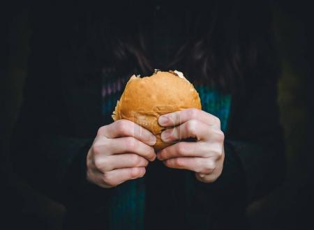 The concept of hunger and poverty. A roll or hamburger in the hands of a close-up.