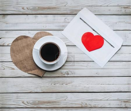 Cup of coffee and an envelope with a letter of love. The concept of St. Valentine's Day. Envelope with heart inside. Envelope on a wooden background.