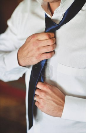 Closeup of man in white shirt adjusts his tie. Dress in formal wear