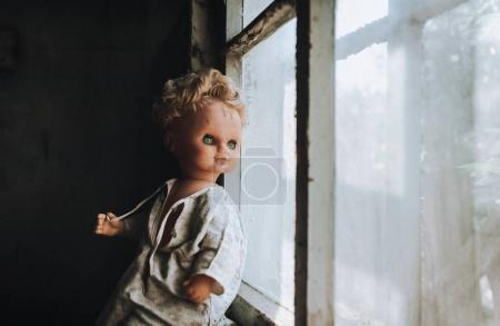 The old doll sitting in the doorway. Old wooden shed. Fear, hate, horror, loneliness. Vintage.