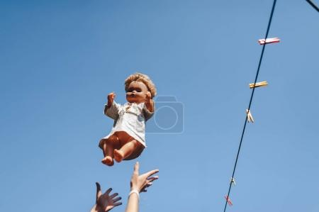 Female hands hold an old doll against the sky