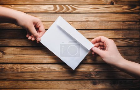 Brown envelope holds the child's hands. Envelope on wooden background