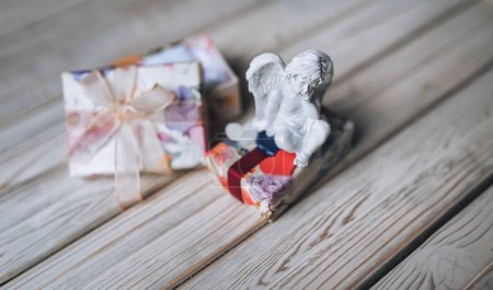 Small cupid with wings sits in pensive posture with little gifts. Amur. Cupid figure. Vintage Cupid. Boy angel. Valentine's Day.