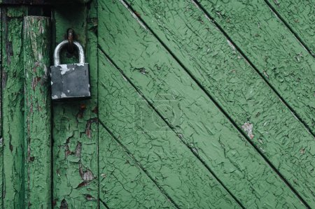 Old wooden green door with a padlock. Fragment close-up.