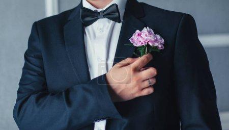Foto de Primer plano del joven en traje ajustando boutonniere - Imagen libre de derechos