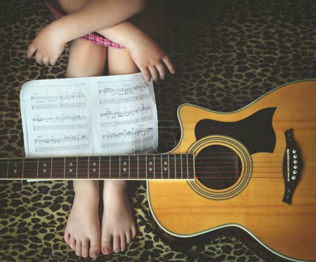 Little girl with a guitar and musical notes sitting on the couch