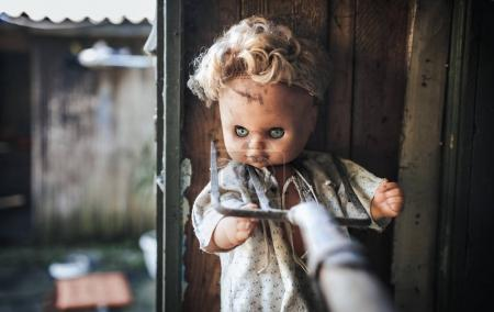 Old doll pressed to the wall with garden forks. Aggression, cruelty, fear.