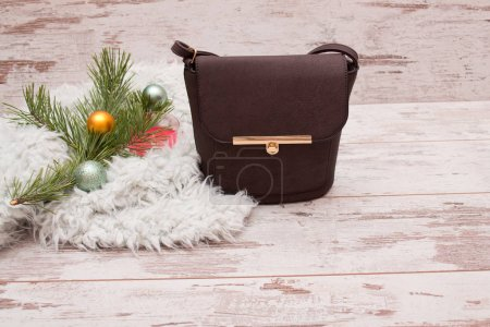 Small brown female handbag on a wooden background, fir branch with decorations. Fashion concept with space for text