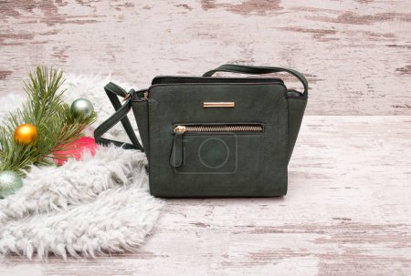 Small green female handbag on a wooden background, fir branch with decorations. Fashion concept with space for text