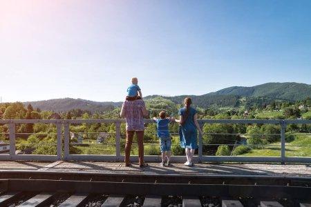 Photo pour La famille se tient sur la plate-forme sur fond naturel. Attente du train. Voyage avec la famille - image libre de droit