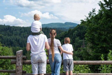 Photo pour Famille de quatre personnes sur fond naturel. Vue de dos. Repos actif. - image libre de droit