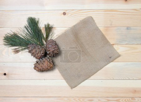The cedar branch with cones on vintage fabrics on a wooden texture