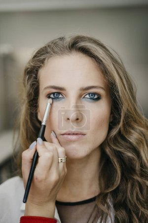 Young girl doing make-up in a salon