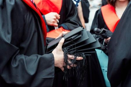 Man holding a lot of mortar boards in focus on a summer day in O