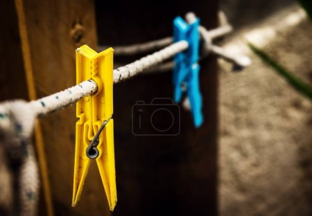 Two different wash pins yellow and blue hanging on rope