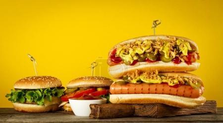 Photo pour Savoureux hot dog traditionnel classique sur panneau en bois sur fond jaune . - image libre de droit
