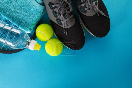 Photo for Healthy Life Sport Concept. Sneakers with Tennis Balls, Towel and Bottle of Water on Bright Blue Background. Copy Space. - Royalty Free Image