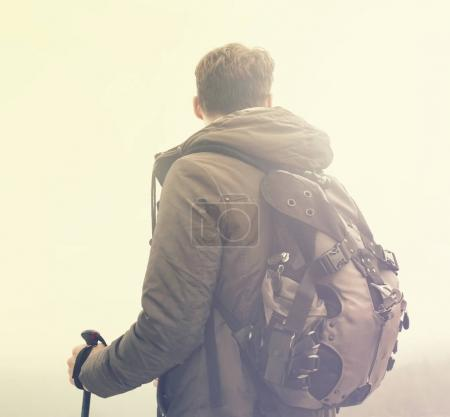 Young hiking man sportsman or traveler with backpack staying.