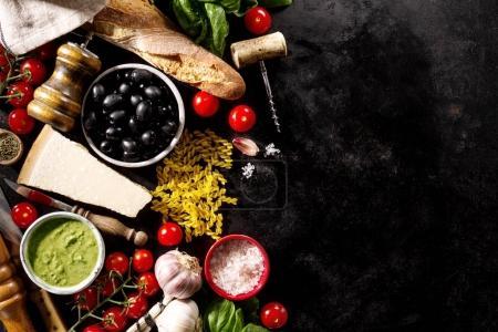 Tasty fresh appetizing italian food ingredients on dark background