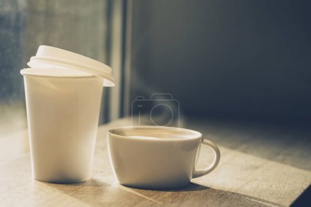 Different cups of coffee - ceramic mug and paper cup to go on wo