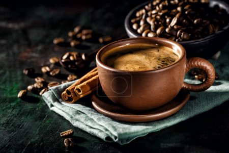 Photo for Cup of freshly brewed coffee composed on black with coffee beans and cinnamon sticks. - Royalty Free Image