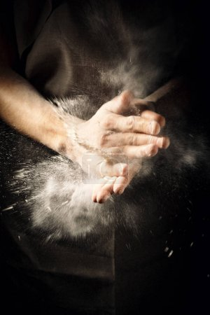 Photo for Unrecognizable cook clapping hands with flour while making dough. - Royalty Free Image