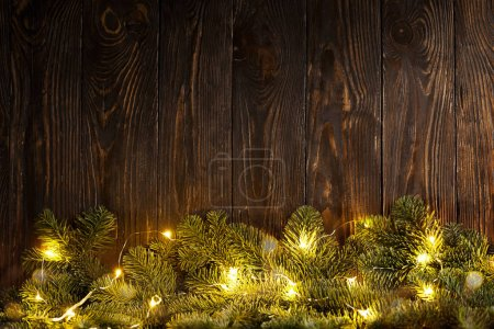 Photo for From above fir tree branches decorated for Christmas with lighting garland. - Royalty Free Image