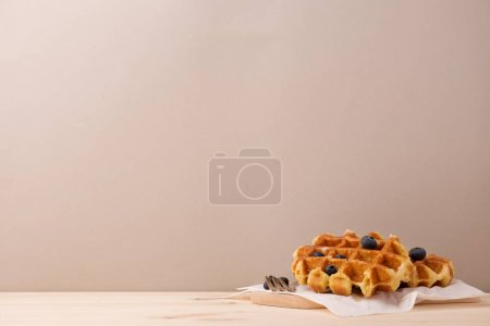 Photo for Tasty fresh baked waffles served with berries on beige background. - Royalty Free Image