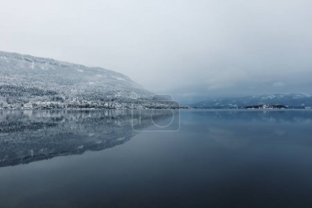 Photo pour View to calm beautiful lake and mountains in foggy winter day. - image libre de droit