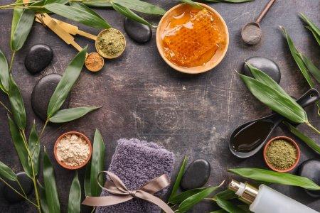 Foto de Vista superior de diversos artículos para spa y hojas verdes sobre mesa áspera. - Imagen libre de derechos