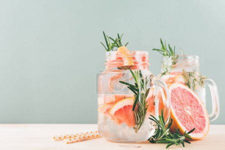 Photo pour Two drinking jars with refreshing icy grapefruit water on gray background. - image libre de droit