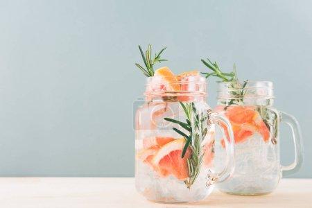 Photo pour Deux pots de boire avec une rafraîchissante eau de pamplemousse glacial sur fond gris. - image libre de droit