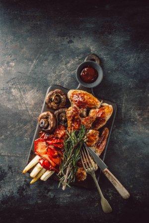 Foto de Desde arriba de los pedazos de pollo asado con salsa y verduras sabrosas sobre fondo áspero. - Imagen libre de derechos