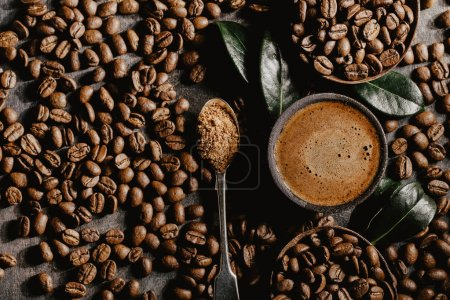 Photo for Top view of cup of brewed black coffee arranged with plenty of brown beans and green coffee leaves. - Royalty Free Image