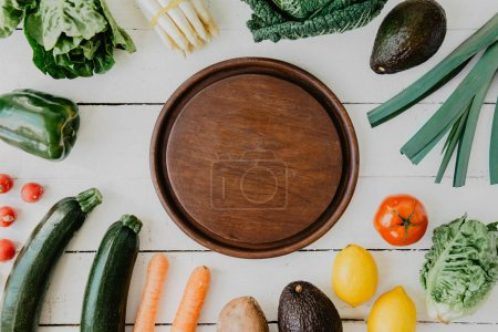 Photo for Flat lay of organized composition of fresh vegetable on white with round plate in middle. - Royalty Free Image